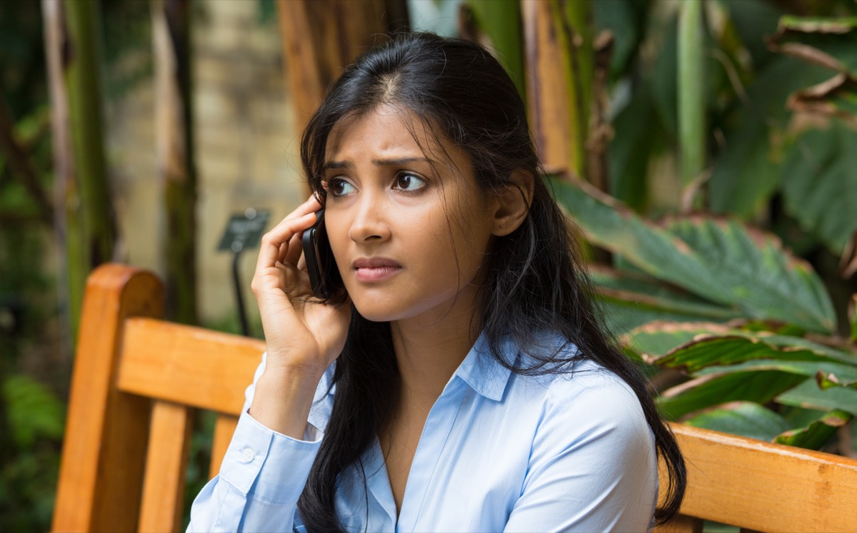 young woman sitting on wooden bench looking annoyed while talking on a smartphone