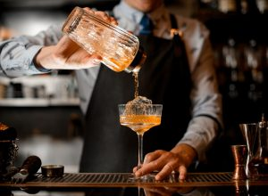 Bartender pouring a drink into a glass