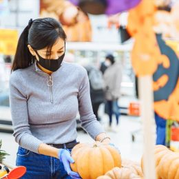 Young woman wearing a protective mask and gloves choosing pumpkins for Halloween in a supermarket. Reality 2020.