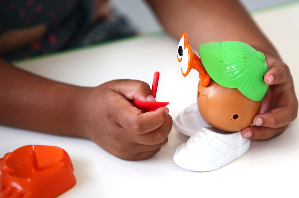 A child playing with a Potato Head toy