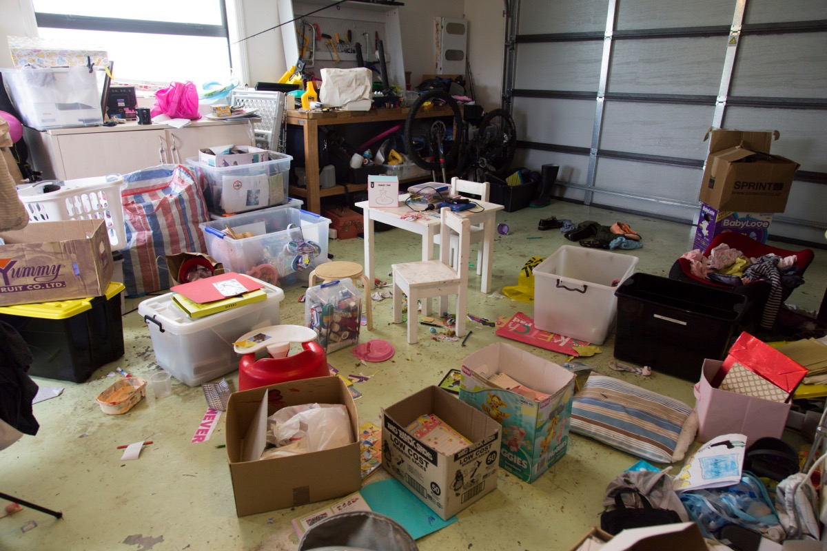 cluttered garage with boxes and mess on the floor