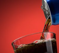 Pouring a refreshing diet soda from a can into a glass