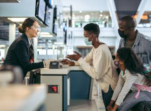 A family wearing face masks speaks with a ticket agent at the airport