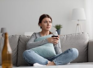 Sad frustrated tired caucasian pretty millennial woman with glass of wine suffering from depression, loneliness and stress at home, empty space. Bad relationships, problems, addiction and crisis