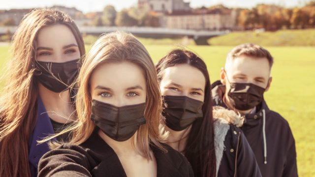 A group of young friends wearing face masks outside