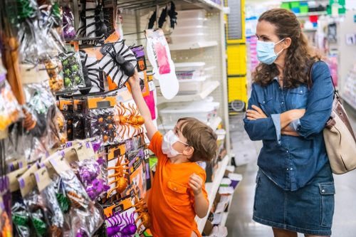 little boy shopping for halloween toys wearing protective mask