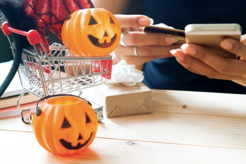 Halloween accessories and costumes on a shopping cart with a woman using a cellphone and a credit card, Happy Halloween