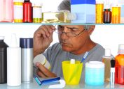 Man reading a prescription label in front of his bathroom Medicine Cabinet