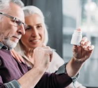 older man and woman looking at pill bottle