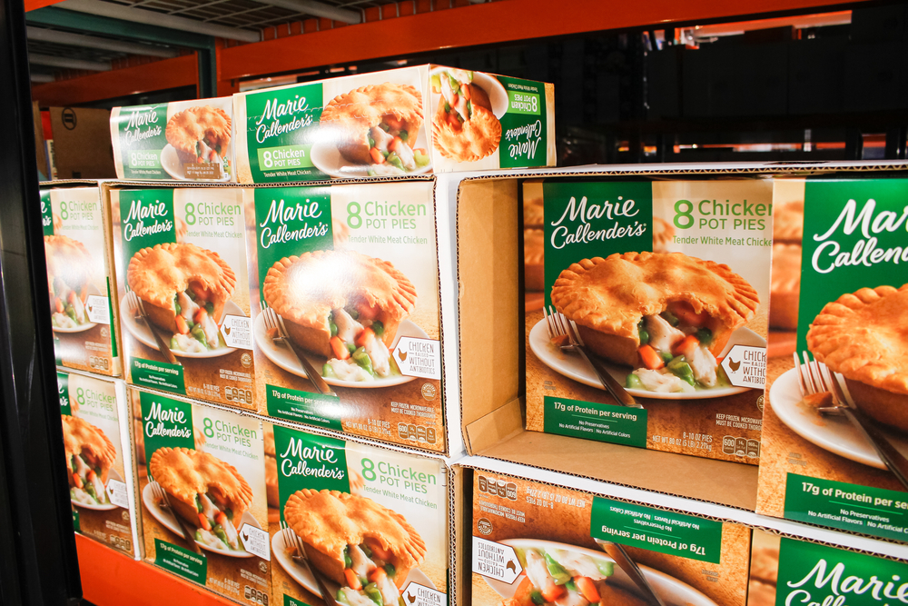 Boxes of Marie Callender's chicken pot pies sitting in the freezer section of a grocery store