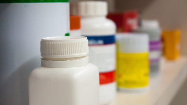 open medicine cabinet full of prescription bottles