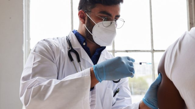 Young male doctor wearing a protective face mask vaccinating a male patient in a medical clinic