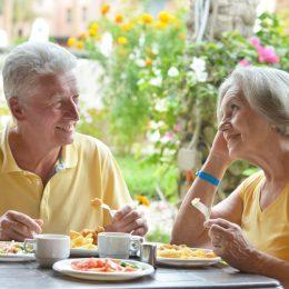 older couple eating breakfast outdoors