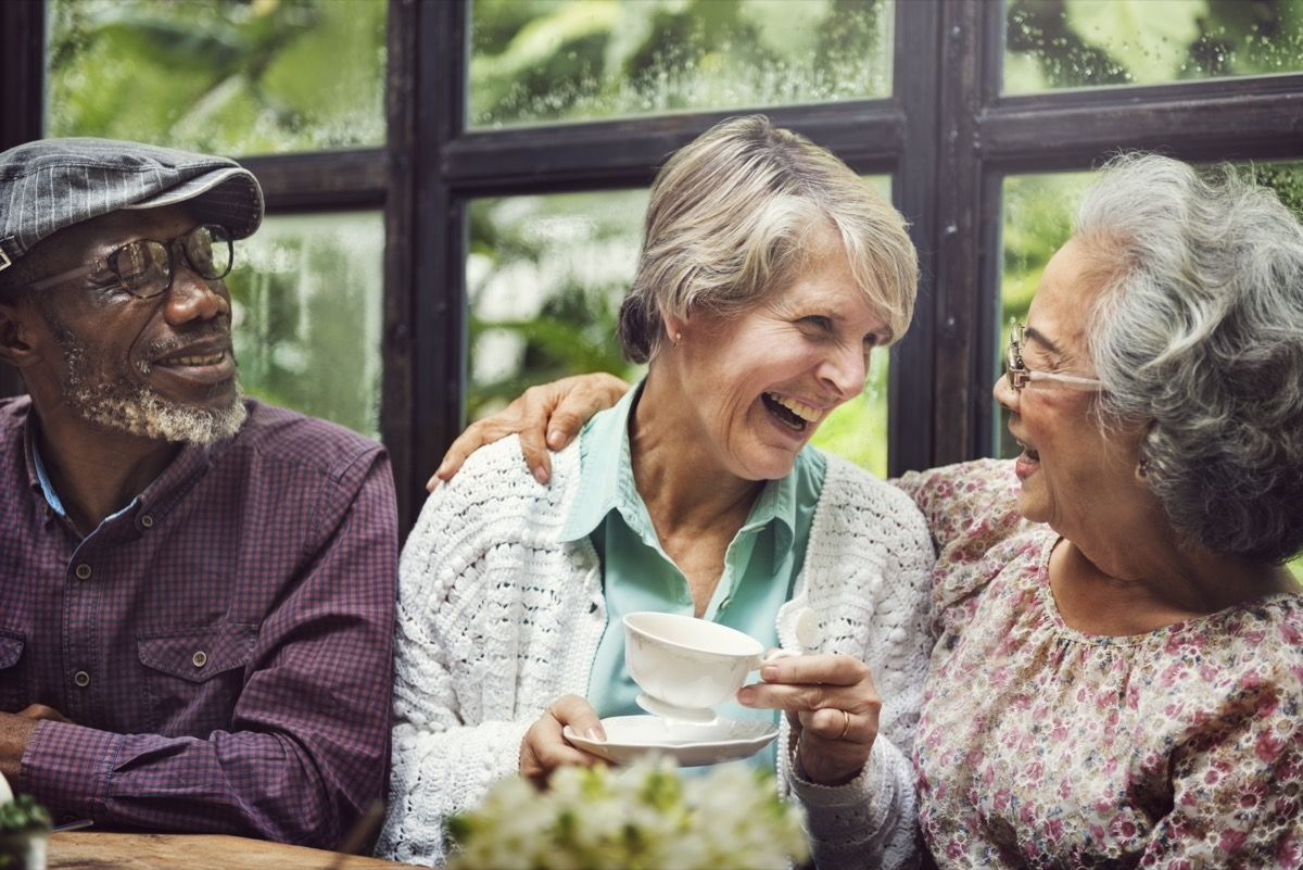 older adult friends laughing together over tea in a restaurant