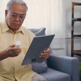 older man holding pill bottle on ipad
