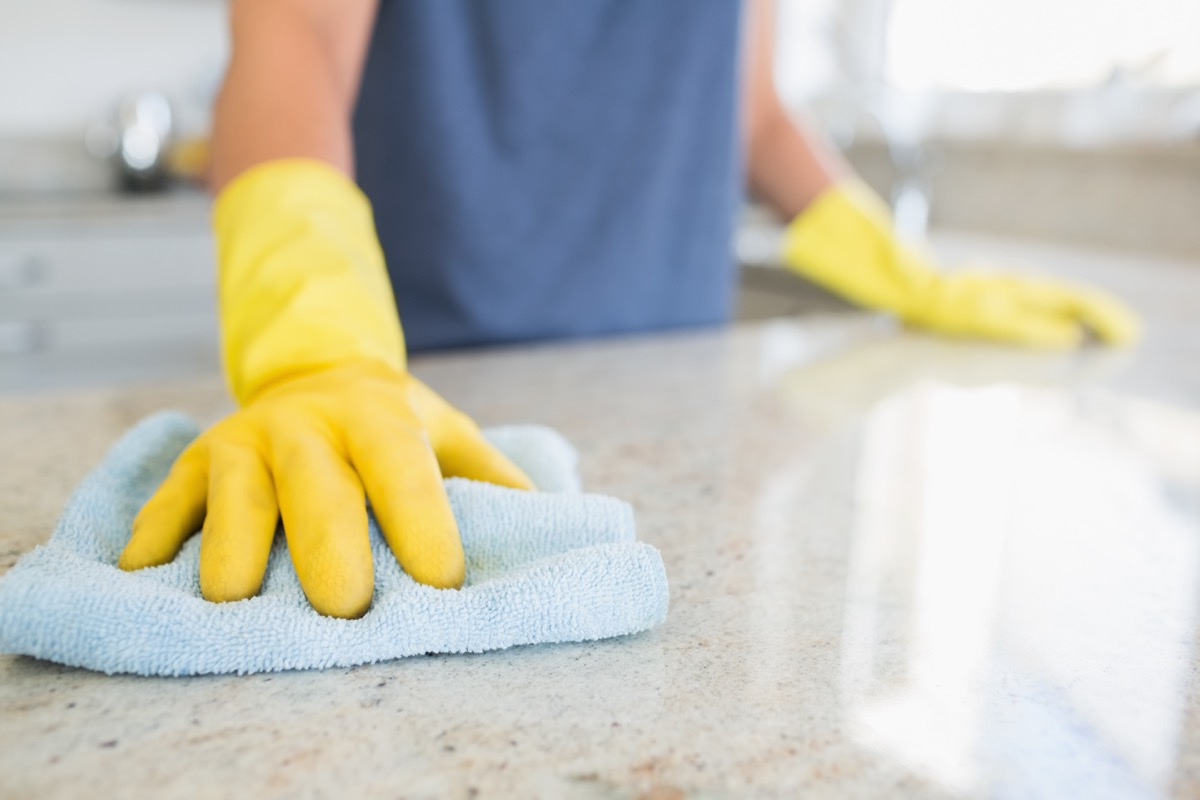 person wearing gloves cleaning kitchen counter