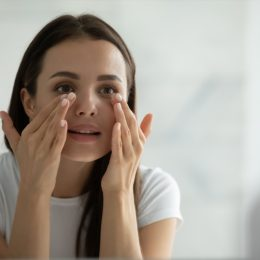Woman looking at her eyes in the mirror