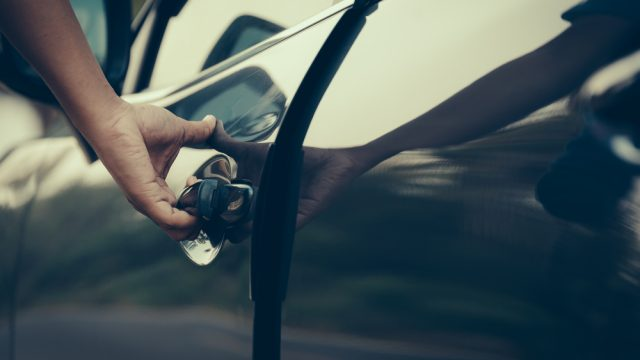 A close up of a person opening a car door