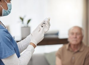 Shot of a young nurse giving an elderly man the vaccine at home