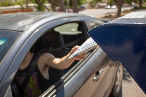 Albuquerque, New Mexico / USA - May 25 2020: Man drops off mail package with eBay envelope from his car at a USPS mail drop box outside the post office