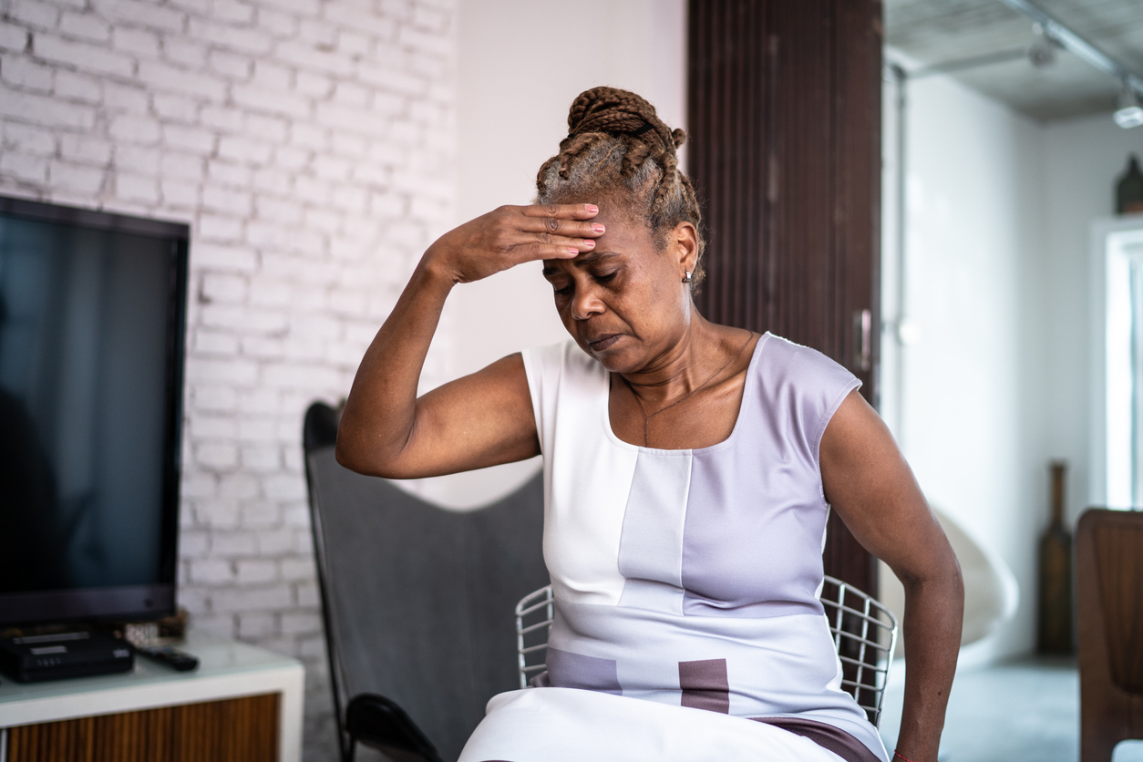 A senior woman sitting in a chair after feeling dizzy