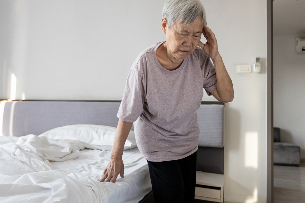 A senior woman standing up from bed and feeling dizzy