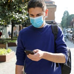Man walking out side wearing a mask and looking at phone