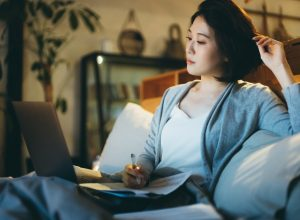 woman sitting on the bed, working from home using laptop and handling paperworks