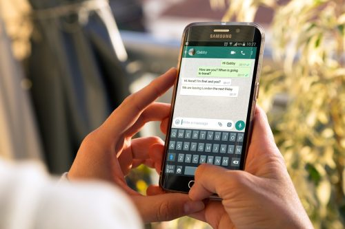 ROSARIO, ARGENTINA - 8 DE AGOSTO DE 2017: Chica con smartphone en manos y conversación de WhatsApp en pantalla.  Mujer joven, milenaria, charlando.  La tecnologia.  Comunicaciones.  Red social.