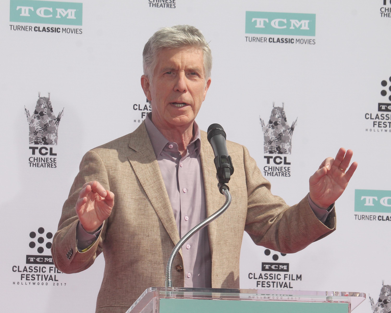 TV host Tom Bergeron speaking at a podium.