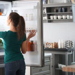 young woman opening fridge door