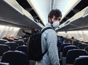 Shot of a young man wearing a mask and boarding an airplane