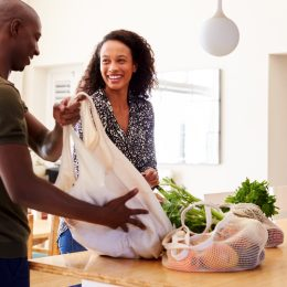 young couple unpacking groceries at home