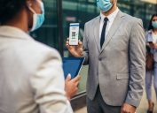 Male office worker in safety mask showing electronic vaccination certificate to employer