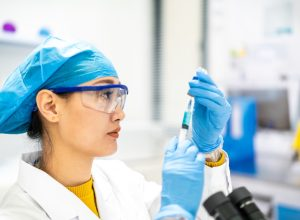 woman scientist uses a syringe in a lab