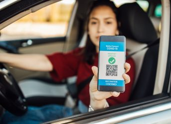 Young woman in a car showing a smartphone with a digital international certificate of Covid-19 Vaccination.