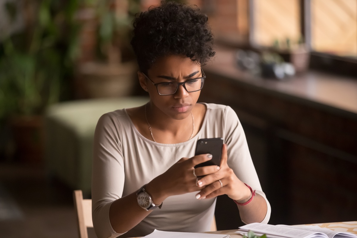 young woman looking confused and looking at cell phone