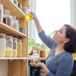 woman reaching for oil in pantry