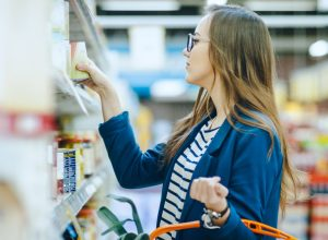 A young woman shopping in a grocery store while holding a basket