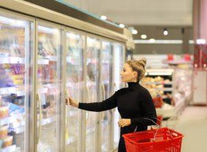 young woman in black turtleneck opening supermarket freezer
