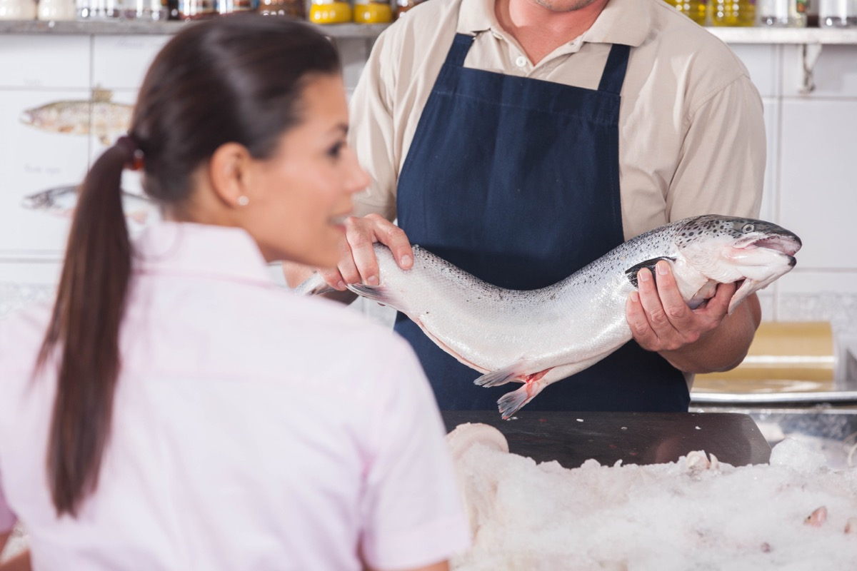 Young brunette woman selecting fish in a restaurant
