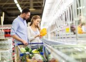 woman and man shopping in supermarket freezer