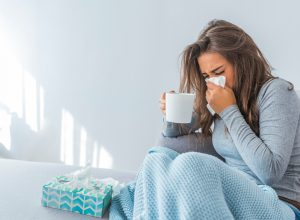 A woman sitting on the couch while sick and blowing her nose into a tissue while holding a mug
