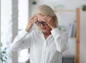 A senior woman standing up and grabbing her head from dizziness or a headache