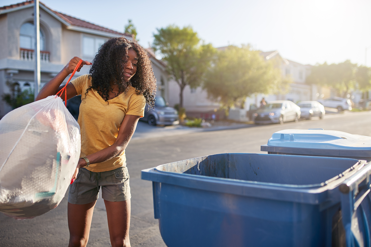 Woman taking out the trash in neighborhood