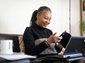 middle-aged woman wearing a black turtleneck with her hair in dreadlocks looking at phone and computer on couch