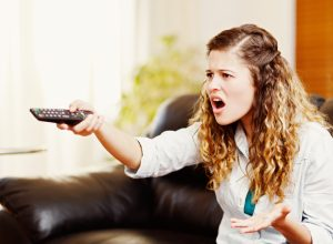 A young woman angrily pointing a remote at the TV