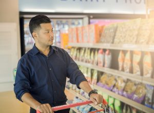 young man in black shirt grocery shopping in snack aisle