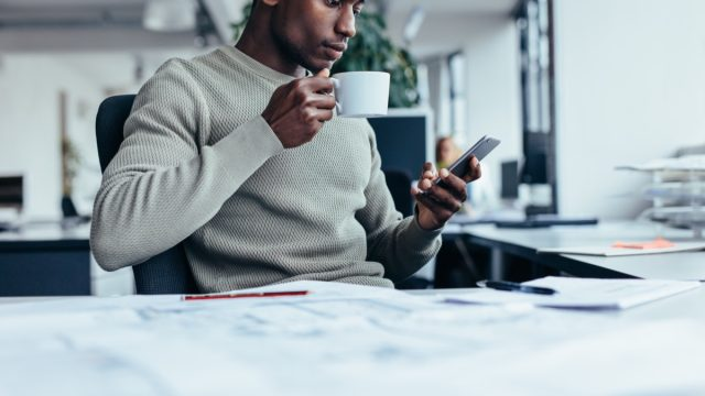 young man at office looking at smartphone