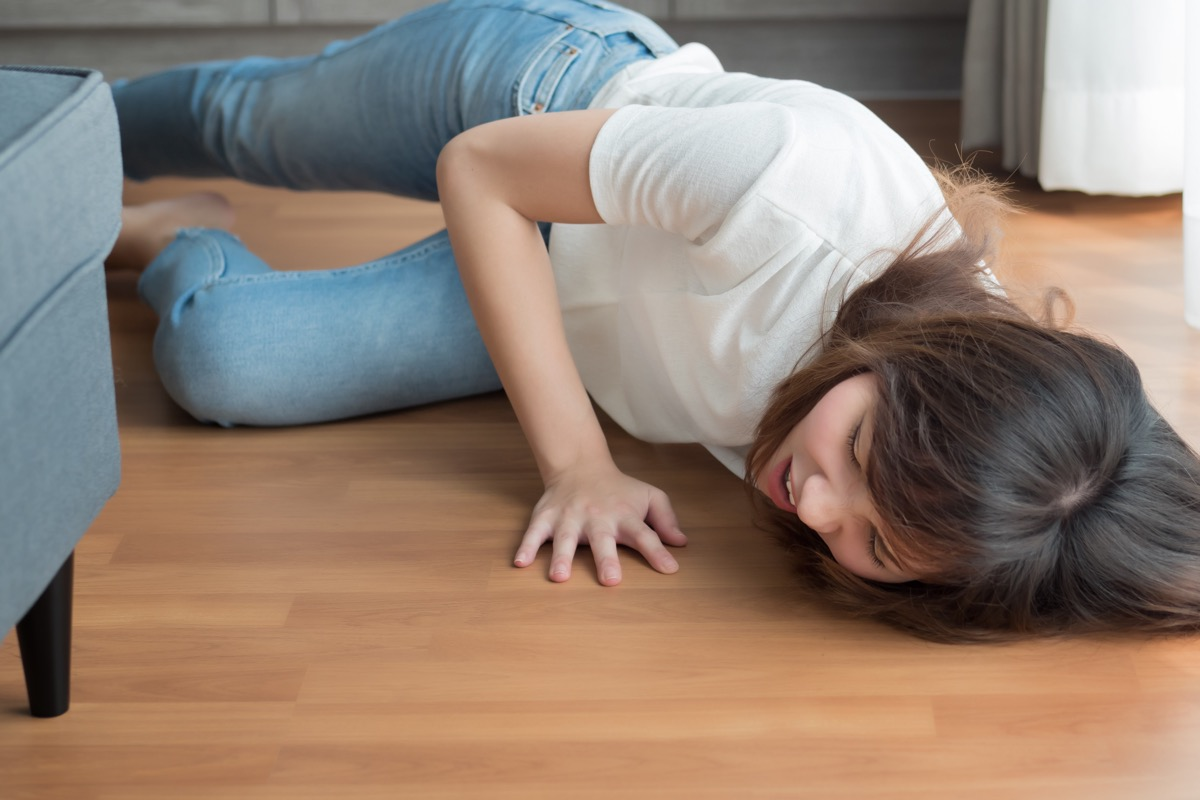 young woman in jeans and a white t-shirt falling on the floor of her home